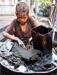 Eight-year-old Gudia collects used engine oil at an auto workshop in Jammu. She is among the estimated 16 million children growing up without education or skills