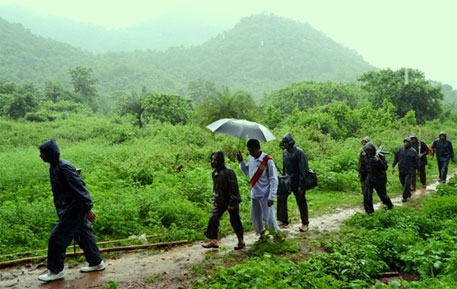 "District judge Sarat Chandra Misra walks up the forest path to Kesarpadi, his ""orderly"" holding the umbrella, under a tight security cordon (Photos: Sayantan Bera)"