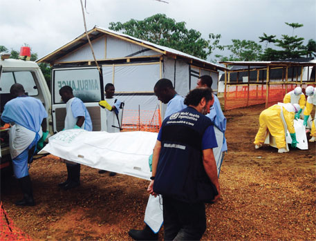 Volunteers carry bodies at an Ebola treatment centre run by Medecins Sans Frontieres in Kailahun, Sierra Leone, on July 18