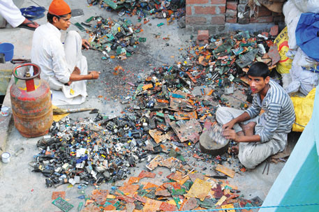 Dismantlers separate printed circuit boards from electronic waste at a workshop in Moradabad