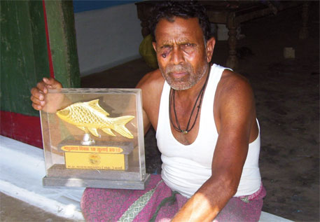 Raghubir holds a trophy his cooperative received last year for catching 18 tonnes of fish; 10 years ago 25 tonnes was the minimum catch of any cooperative