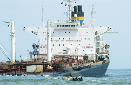 A boat sails on August 13, 2003, past grounded Greek oil tanker Tasman Spirit, which had run aground at Karachi harbour a month ago