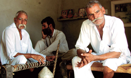 With guar returns, farmers like Ram Karan Charan (left, with clasped hands)