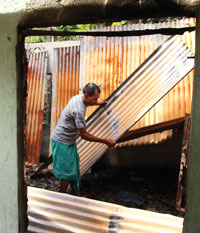 Kalidas Bramho of Bangaldo Part II village inspects tin sheets of his house gutted during the riot on July 23