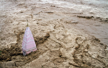 A temple stands amidst the waters of the overflowing Tawi river during heavy rains in Jammu on September 6