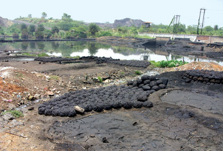 Blatantly flouting norms, SAIL Durgapur's coke oven discharges hazardous tar waste, which people collect and use as cooking fuel; (right) Tata Steel discharges coal ash slurry into the Kharkai river in Jamshedpur