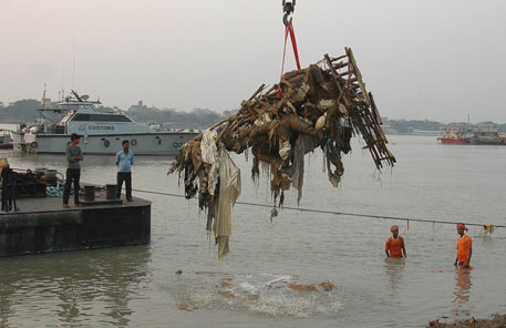 In Kolkata, cranes are positioned on a barge and on the river banks to lift out the idols immediately after immersion
