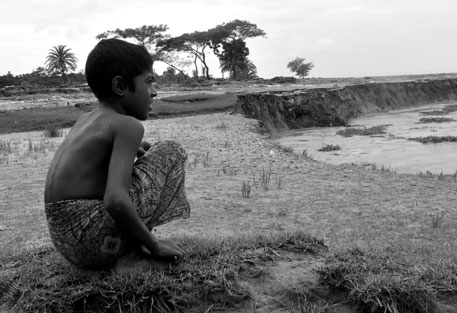 A boy from Burhanuddin sub-division of Bhola island district by the banks of the Meghna river. People in the area say erosion and inundation has aggravated in the recent past