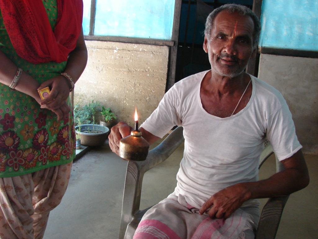 Durga Prasad Parajuli shows the kerosene lamp his family has to use despite having an electricity connection (Credit: Karnika Bahuguna/CSE)
