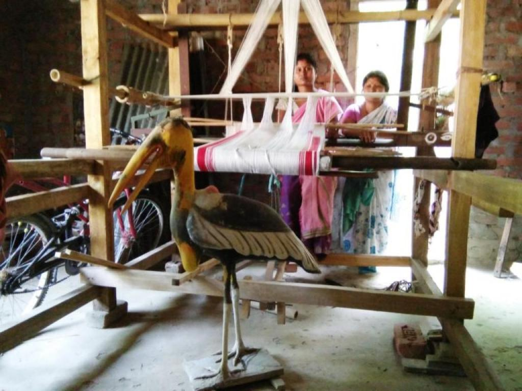 Members of the self-help weaving group with Greater Adjutant statue and handloom donated by the government. Credit: Purnima Barman