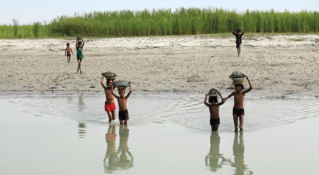 सुपौल में दोनों तटबंधों के बीच बने अपने घरों को लीपने के लिए मिट्टी खोदकर लाते बच्चे (फोटो: विकास चौधरी)