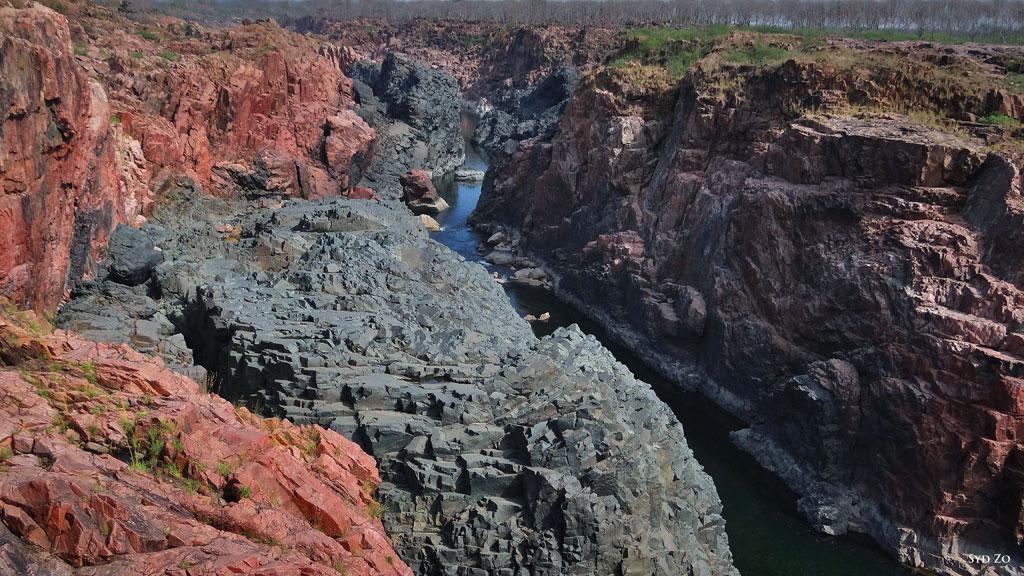 मध्य प्रदेश में केन नदी, जहां आप एक ही स्थान पर कई प्रकार की चट्टानें देख सकते हैं। अग्रभूमि में सफेद-भूरे चट्टान एक पका हुआ कैल्शियम युक्त चट्टान है जो लगभग 120 मिलियन वर्ष पुराना है। यह स्लेटी शिस्ट के ऊपर की एक परत है, जो लगभग 550 मिलियन वर्ष पुराना है। गुलाबी चट्टान क्वार्टजाइट है, जो लगभग 90 से 65 मिलियन वर्ष पुराना है