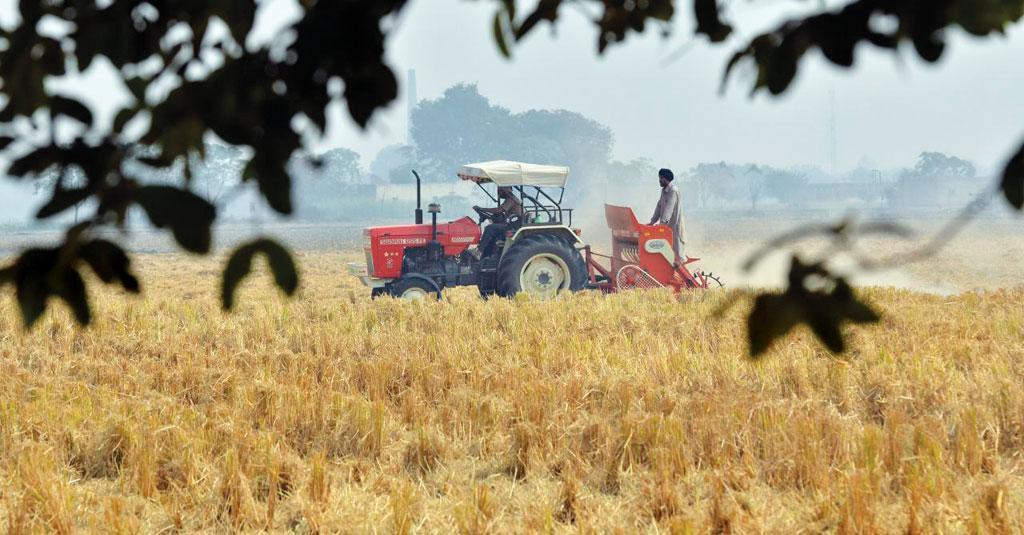 Farmers in Sangrur district, Punjab, plant wheat in a field of rice stubble using a tractor-pulled Happy Seeder. The machine eliminates the need to burn rice residues after harvest (Photo: Neil Palmer)