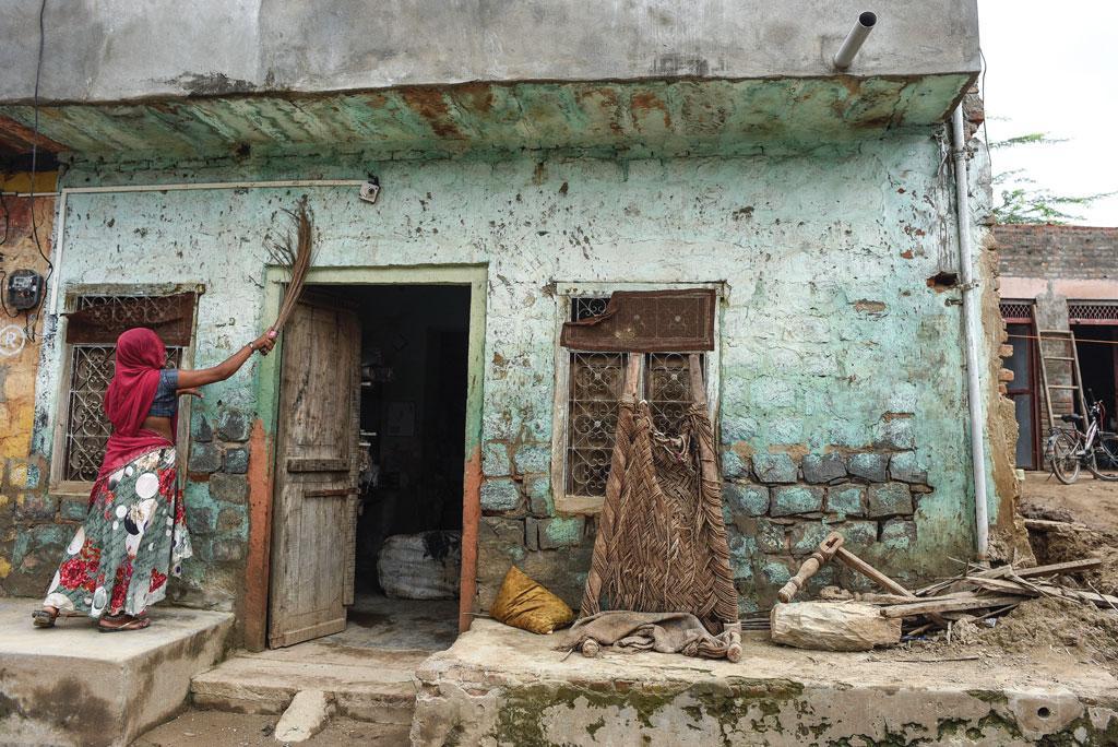 पाली जिले के डोला गांव में यह घर बाढ़ में पूरी तरह से डूब गया था। पानी उतरने के बाद अपने घर को साफ करती एक महिला