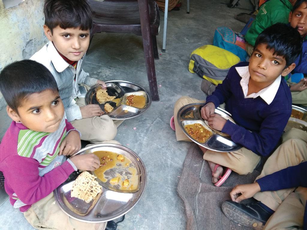 हरियाणा के फरीदाबाद के जिले के अजरौंदा गांव में स्थित प्राइमरी स्कूल में मिड डे मील योजना के तहत मिलने वाला भोजन करते छात्र (अर्चना)