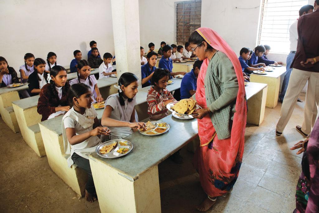 इंदौर के बाहरी इलाके में स्थित एक माध्यमिक विद्यालय में छात्र-छात्राओं को मिड डे मील परोसती एक सहायिका (विकास चौधरी / सीएसई )