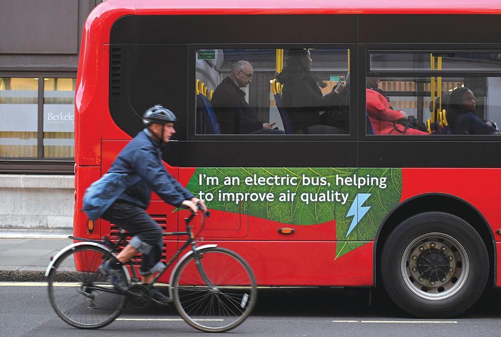 लंदन में एक साइकिल सवार सरकारी इलेक्ट्रिक बस के पास से गुजरता हुआ। इसी दिन लंदन के मेयर सादिक खान ने लंदन शहर के सर्वाधिक  प्रदूषणकारी वाहनों पर कर लगाने का फैसला लिया (रॉयटर्स)