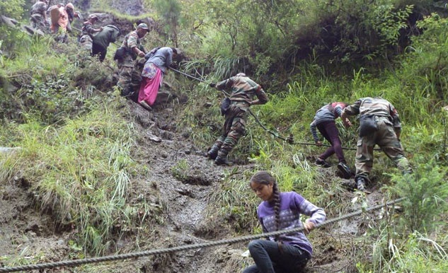 Army personanel evacuating pilgrims by foot on route to Kedarnath