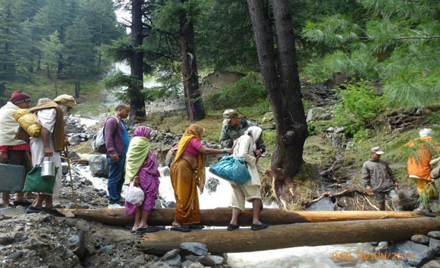 Army personnel evacuated 600 people across a rivulet by laying a temporary bridge made of wooden logs on rout