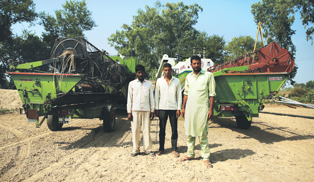 Haryana farmer Jagdeesh Singh (extreme right) travels to neighbouring states with his farm machines during harvesting season (Photo: Vikas Choudhary)