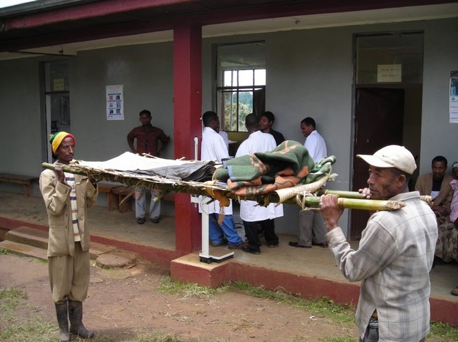 Men prepare a stretcher to carry a woman. Image supplied