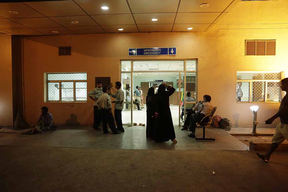Relatives of dengue patients wait near the emergency ward of the Ram Manohar Lohia Hospital in New Delhi