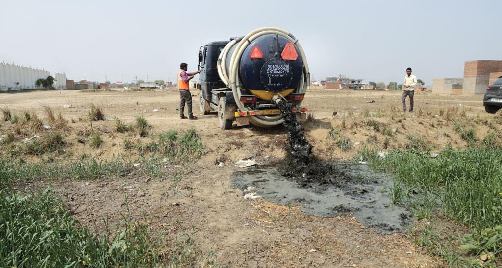 A vacuum tanker dumps untreated faecal sludge in a wheat field in the National Capital Region