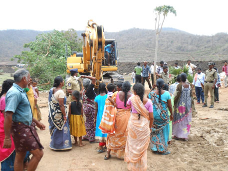 Evicted village residents stand by as officials demolish houses