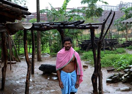 Daka majhi poses for the camera outside his house next to Vedanta's alumina refinery in Lanjigarh