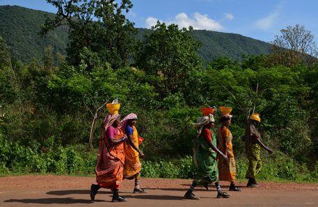 Women workers return from Vedanta's alumina refinery in Lanjigarh on the foothills of Niyamgiri