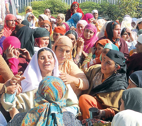 Relatives of slain sarpanch Mohammad Amin mourn his death at his funeral in April, 2014
