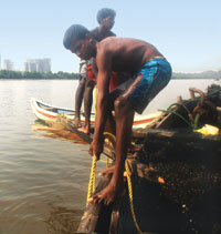 Workers carry beach sand minerals on a boat