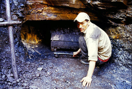 A worker squats to pull out a fully laden tray of coal from a hole. When the coal within the pit exhausts, horizontal tunnels are dug through which workers burrow to find coal. Many workers narrate incidents of tunnel roofs collapsing and trapping the workers inside (photograph by P Madhavan)