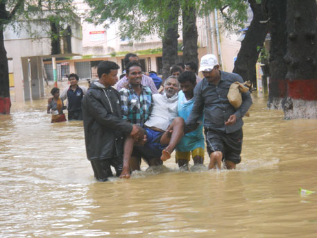 People rescue an old man in Baripada town, headquarters of Mayurbhanj district