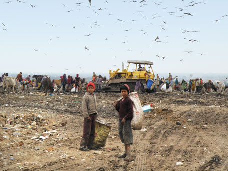 12-year-old Bittoo (right) bleeds and often catches infection as he rummages through piles of garbage at the Bhalswa landfill with bare hands