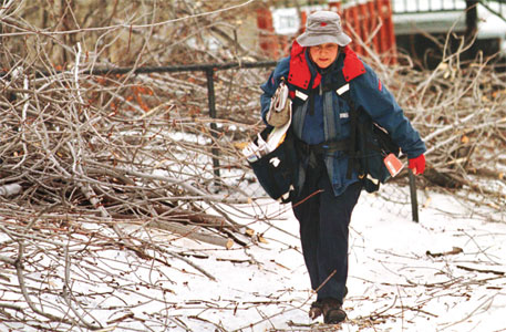 Canada Post letter carrier Marie Lamprom navigates an icy sidewalk
