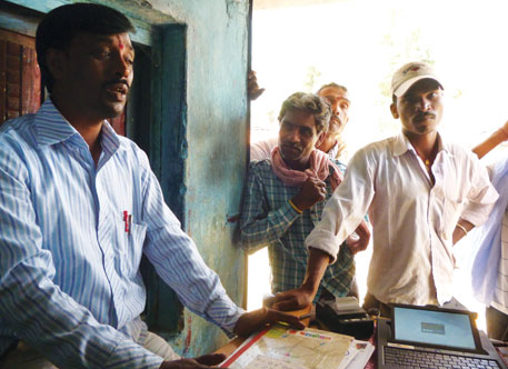 "Hem Raj Prasad Mishra (left) runs a kindergarten school in Barkoti Kalan in Madhya Pradesh. Each time he goes to the bank kiosk to open an account, the banking correspondent's laptop displays nothing more than ""Reconnecting..."" on its screen"