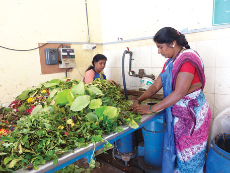 Workers feed segregated garbage into a biomethanisation plant at Bengaluru's K R Puram vegetable market. The municipal corporation has recently set up six such plants in the city