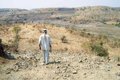 A farmer goes down to the dry bed of Babhulgaon dam in Osmanabad to fetch his cattle