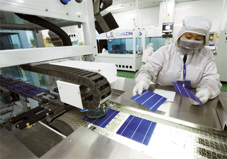 An employee inspects solar modules at LDK Solar's production line in China