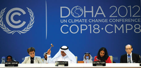 COP-18 president Abdullah Bin Hamad Al-Attiyah drops the gavel, adopting the final texts