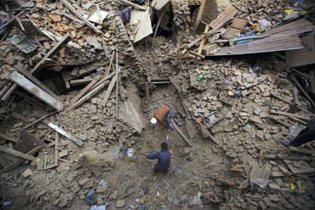 THE DAY AFTER: Rescuers dug with whatever came in handy to find bodies in Nepal on April 26, 2015, after the earthquake devastated the heavily crowded Kathmandu