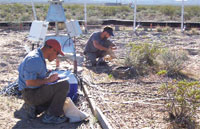 Researchers gather soil samples from a test plot in the Mojave desert