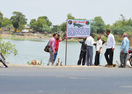 Officials set up a signboard warning about the presence of crocodiles in a pond near Laxmi Vilas Palace in Vadodara