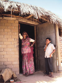Jamuna Devi with her son in her new house in Sheo Village of Barmer district. She lost her house in the flood of 2006