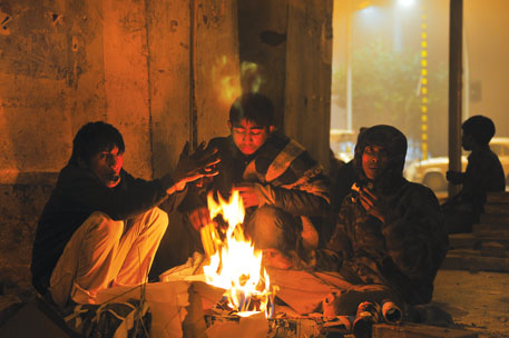 Street children under the Nizamuddin flyover huddle around a bonfire. To save themselves from the biting cold most of the homeless children consume thinner and sleep in groups of four-five, sharing a blanket or two