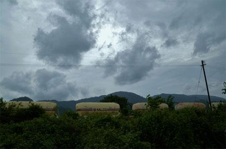 A goods train carrying Alumina from NALCO's Damanjodi refinery in Odisha. On the backdrop are the Niyamgiri hill ranges