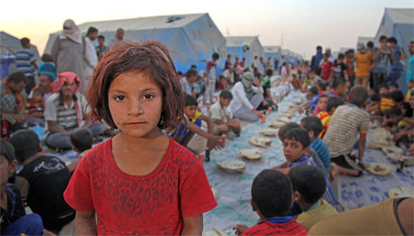 A girl stands among displaced children and adults in the Khazar transit camp Erbil, Iraq (Image courtesy UN)