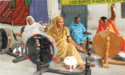 Naseeb Kaur (in white) won the spinning competition at the trinjan festival. Her four daughters grew up wearing clothes from fabric she had spun on this charkha