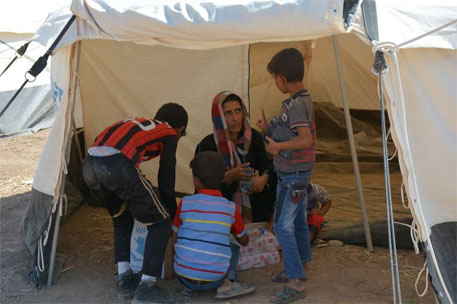 A woman, displaced by conflict in Iraq, with her kids at a UN refugee camp (PhotoL: E Colt/UNHCR)
